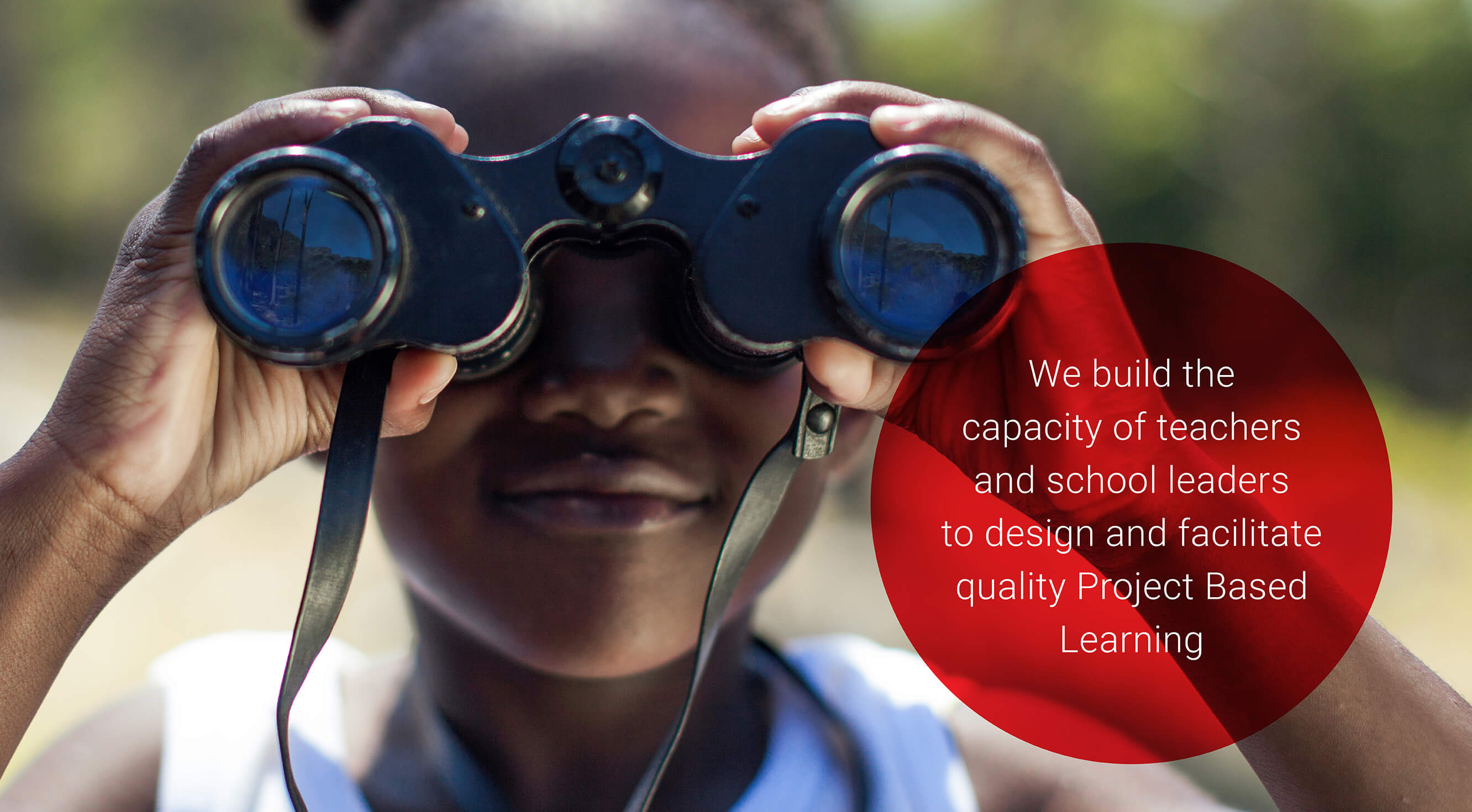 We build the capacity of teachers and school leaders to design and facilitate quality Project Based Learning with a closeup of a young girl looking through binoculars